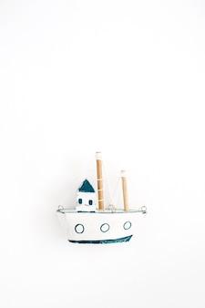 Bateau jouet fait main en bois sur fond blanc. mise à plat, vue de dessus