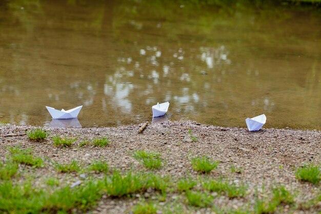 Bateau jouet en papier blanc sur l'eau bleue près du rivage
