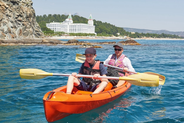 Bateau en kayak près des falaises par une journée ensoleillée. kayak dans une baie tranquille. des vues incroyables. voyage, concept sportif. mode de vie. une famille heureuse.