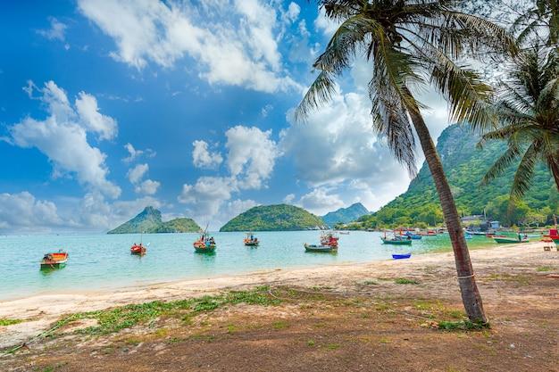 Bateau longtail en bois traditionnel thaïlandais et belle plage de sable