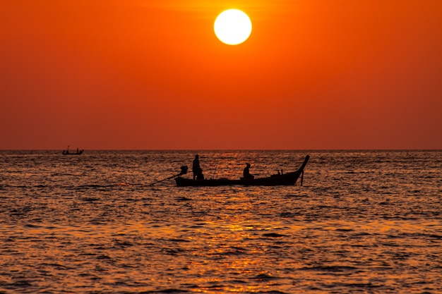 Un bateau à longue queue avec des silhouettes humaines au coucher du soleil à la plage de patong phuket.