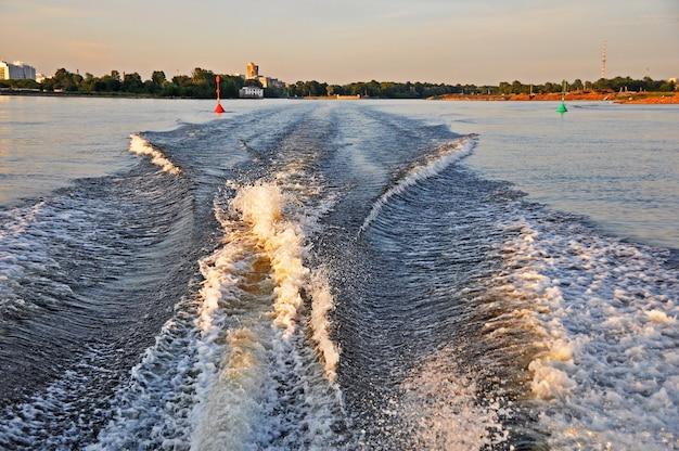 Bateau à moteur blanc vole vite sur les vagues