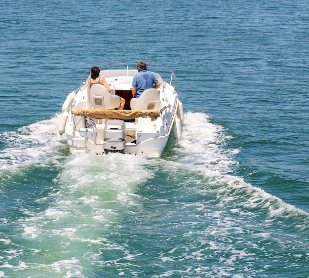 Le bateau à moteur avec couple marié au paysage de la mer