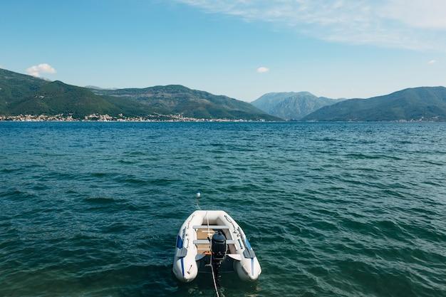 Bateau à moteur gonflable blanc sur la baie de kotor et les montagnes vertes