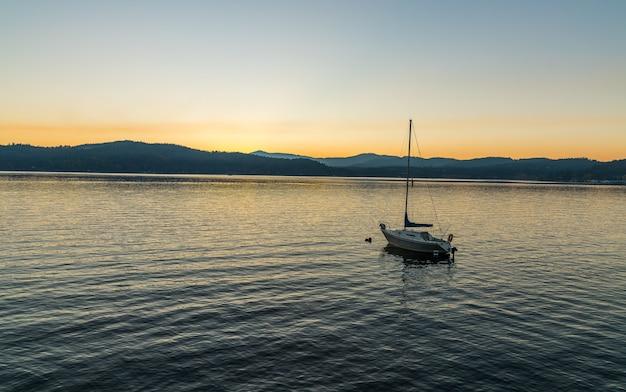Bateau naviguant sur la mer avec des montagnes au loin pendant le coucher du soleil