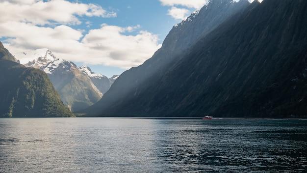 Bateau naviguant à travers le fjord lors d'une journée ensoleillée photo prise à milford sound fiordland nouvelle-zélande