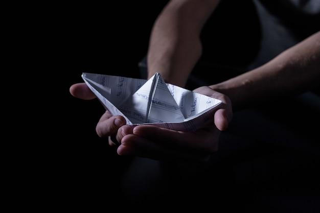 Bateau en papier blanc entre les mains d'un adulte dans une clé sombre, la psychologie