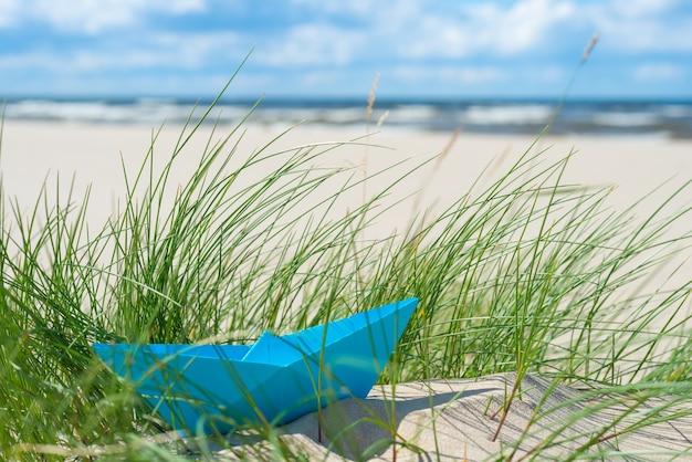 Bateau en papier bleu dans l'herbe