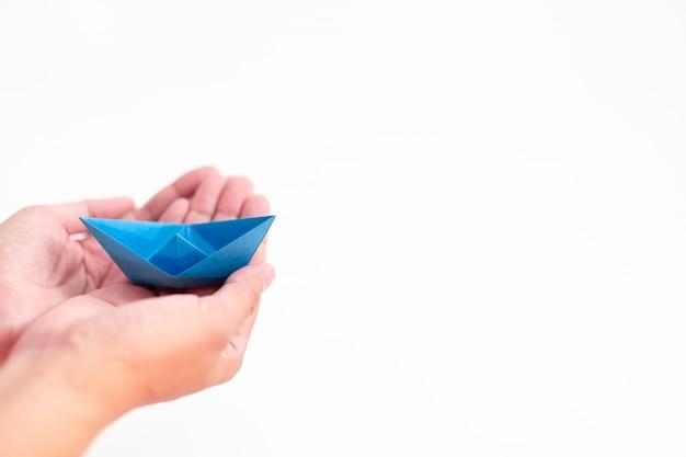 Bateau en papier bleu tenant à la main sur fond blanc, concept d'apprentissage et d'éducation