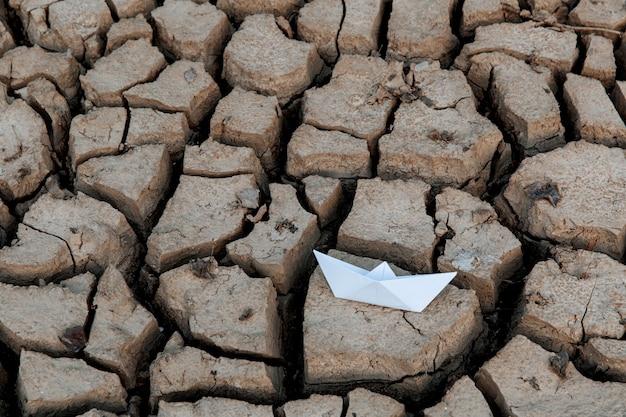 Bateau en papier sur lac asséché, sécheresse conceptuelle, réchauffement climatique.