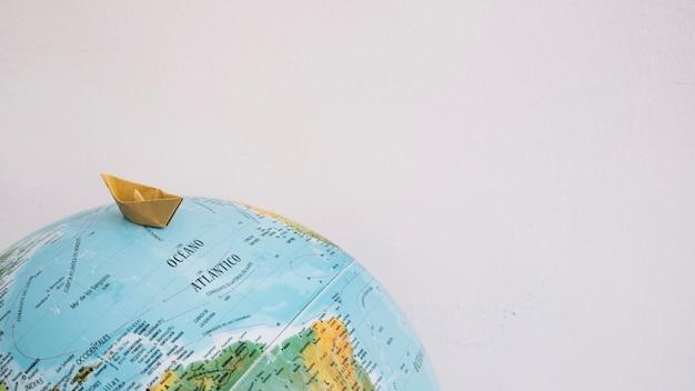 Bateau en papier naviguant sur le globe