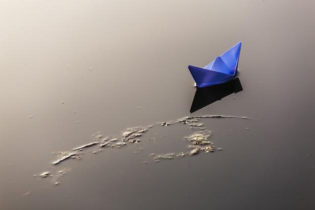 Bateau en papier naviguant sur la surface de l'eau au coucher du soleil