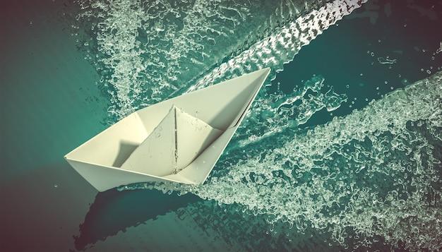 Bateau en papier navigue sur la mer.