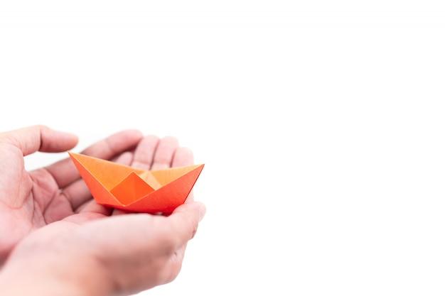 Bateau en papier orange tenant à la main sur fond blanc, concept d'apprentissage et d'éducation