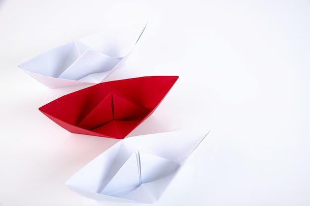 Un bateau en papier rouge entre de nombreux bateaux en papier blanc