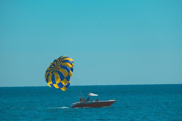 Bateau avec un parachute sur la mer contre le ciel bleu