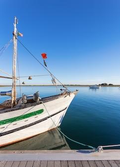 Le bateau de pêche au mât sur le quai. portugal tavira.
