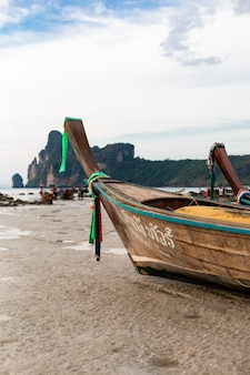 Un bateau de pêche en bois était assis sur le fond sableux de l'océan à marée basse.