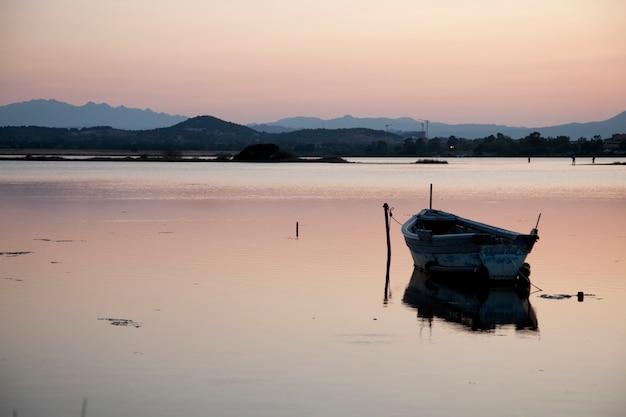 Bateau de pêche dans le lac au coucher du soleil