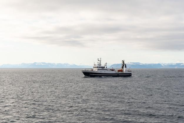 Bateau de pêche dans la mer arctique près de longyearbyen, archipel du svalbard