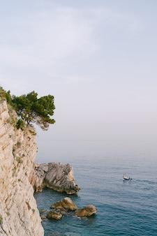 Un bateau de pêche sur l'eau près d'un haut rocher avec un arbre poussant sur la pente
