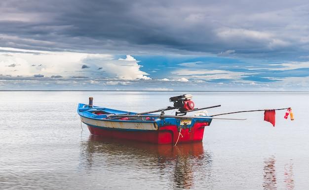 Bateau de pêche avec faible éclairage et ciel sombre.