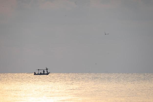 Bateau de pêche local sur la mer avec la scène du lever du soleil dans le parc national de sam roi yot, thaïlande.