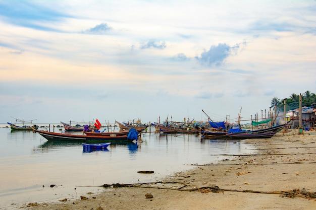 Bateau de pêche en mer, coucher de soleil et silhouettes de bateaux en bois