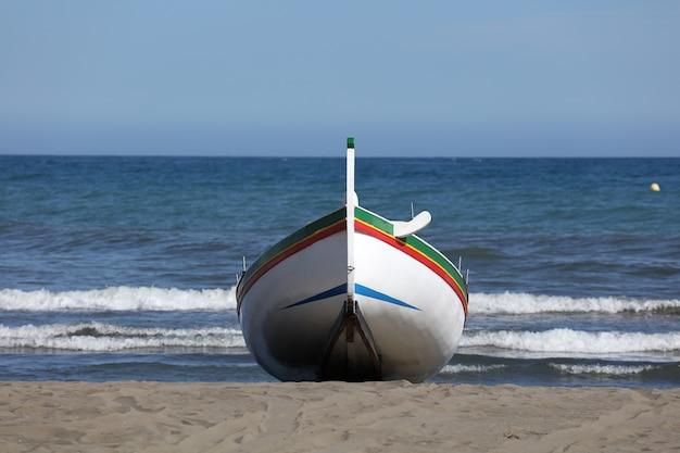 Bateau de pêche sur la plage avec ciel bleu