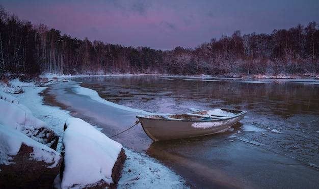 Bateau de pêche solitaire par la rivière gelée au coucher du soleil rose dans la forêt d'hiver