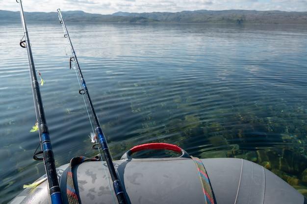 Bateau de pêche à la traîne dans la mer d'un bleu profond avec cannes et moulinets