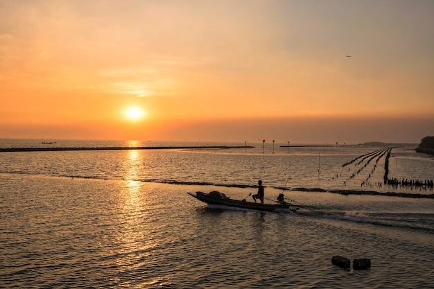 Bateau de pêche à voile pêcheur du port au coucher du soleil à la mer de bang pu