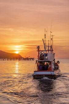 Bateau de pêcheur de basse lumière flottant sur la mer au coucher du soleil doré