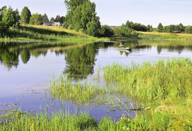 Bateau de pêcheurs sur le lac un canot pneumatique à la surface de l'eau parmi les roseaux