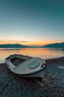 Bateau sur la plage au coucher du soleil.