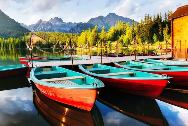 Bateau sur le quai entouré de montagnes. fantastiques shtrbske pleso hautes tatras. slovaquie