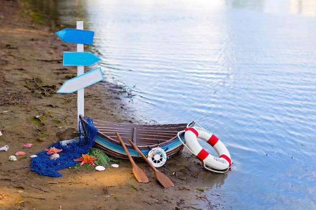Bateau sur la rive sablonneuse de la rivière avec une bouée de sauvetage, des rames, un filet de pêche