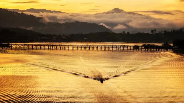 Bateau sur la rivière avec pont et montagnes