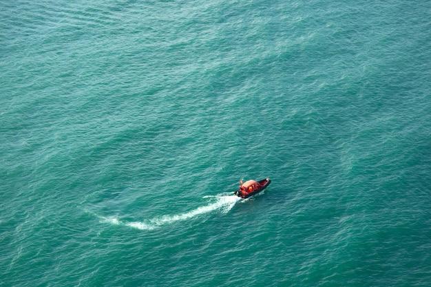 Bateau rouge dans le beau fond de la mer bleue