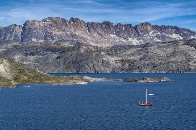 Bateau rouge sur la mer bleue vue montagne grise sous un ciel bleu et blanc