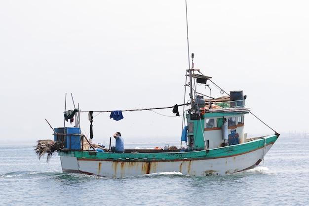 Bateau solitaire naviguant dans la mer de paracas vers le port