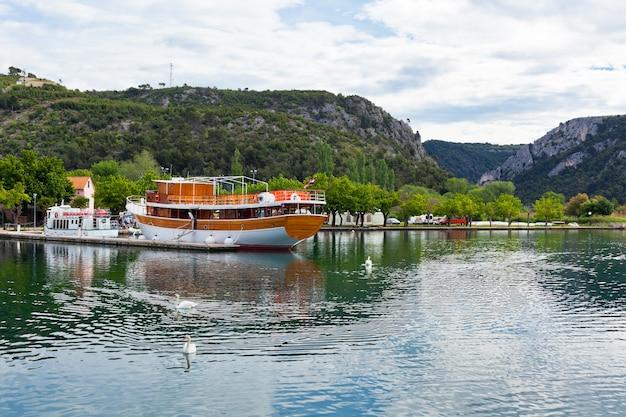 Bateau touristique et cygnes à skradin, croatie. prise de vue horizontale