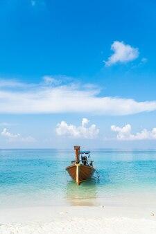 Bateau traditionnel à longue queue sur la mer bleue et la plage de sable jour ciel bleu clair