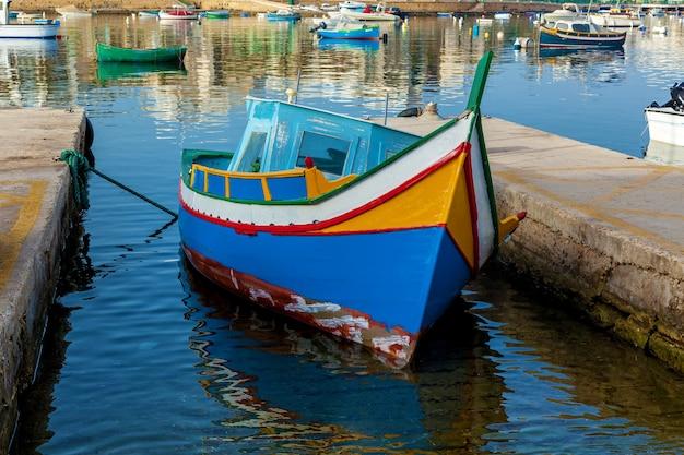 Le bateau traditionnel maltais nommé luzzu est amarré entre deux plaques de pierre
