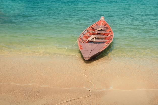 Bateau vide solitaire sur la plage près de la mer avec de l'eau bleu clair. fond tropical de vacances
