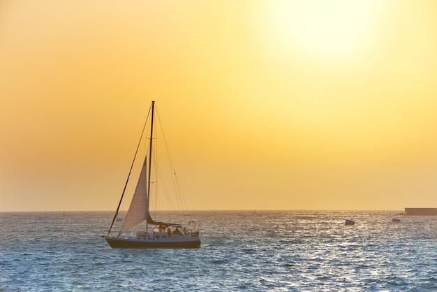 Bateau à voile contre le coucher du soleil sur la mer. paysage marin coloré.