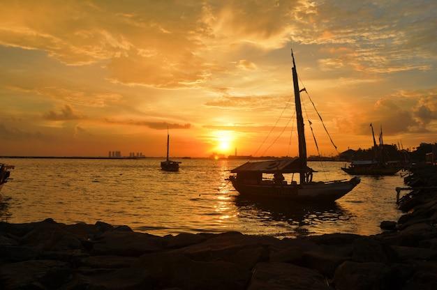 Bateau à voile contre le coucher de soleil