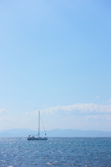 Bateau à voile dans la mer et le ciel bleu avec des nuages, l'île d'egine, grèce