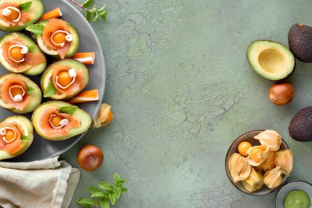 Bateaux d'avocat au saumon fumé, citron, physalis et feuille de menthe, vue de dessus sur vert