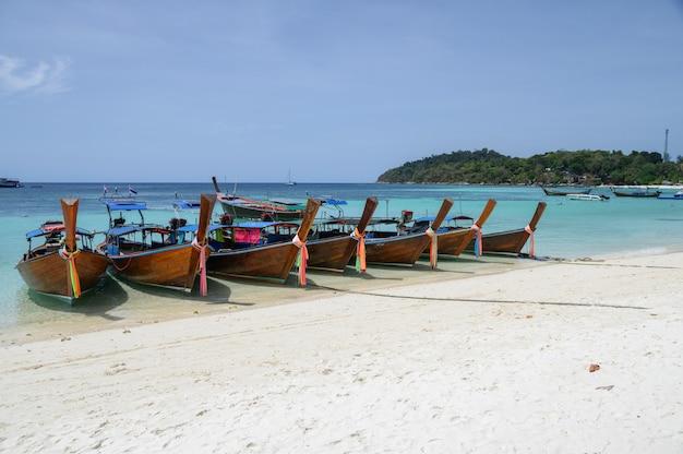 Bateaux en bois à longue queue ancrés sur une plage blanche en mer tropicale